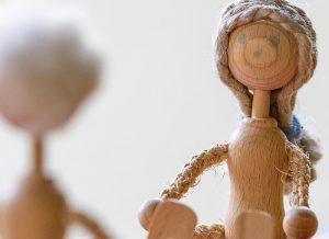 Holzpüppchen auf der Waage als Symbol für eine harmonische Beziehung