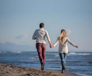 Laufendes Paar am Strand strahlt Freude und Leichtigkeit in der Beziehung aus